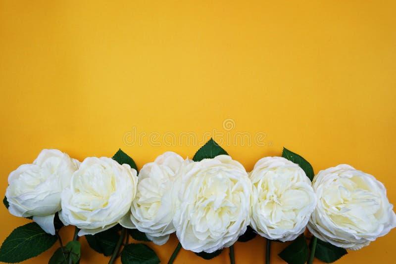 Διαστημικό αντίγραφο με την τεχνητή peony ανθοδέσμη λουλουδιών στο κίτρινο υπόβαθρο στοκ εικόνα