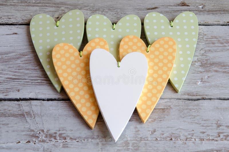 Διαστιγμένος χλωμός - πράσινες καρδιές στο ξύλινο υπόβαθρο στοκ εικόνα με δικαίωμα ελεύθερης χρήσης