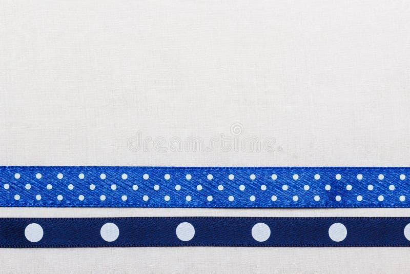Διαστιγμένο μπλε πλαίσιο κορδελλών στο άσπρο ύφασμα στοκ φωτογραφίες