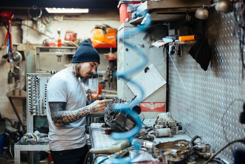 Διαστισμένος μηχανικός που επισκευάζει τα μέρη στο εργαστήριο στοκ φωτογραφία