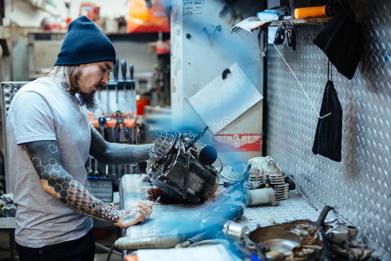 Διαστισμένο άτομο που επισκευάζει τα μέρη αυτοκινήτων στο εργαστήριο στοκ εικόνες