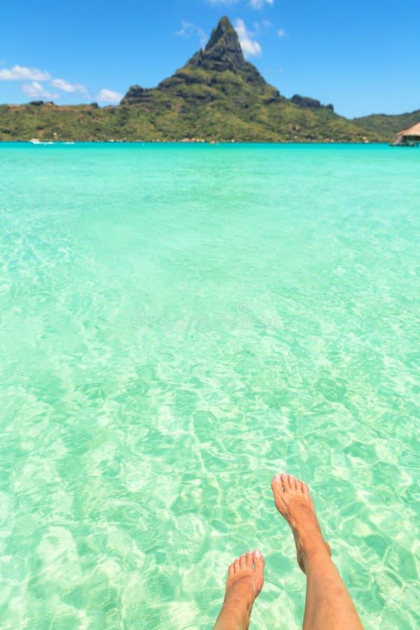 Διασχισμένα τα θηλυκό πόδια πέρα από την τροπικά μπλε λιμνοθάλασσα και Otemanu τοποθετούν, στοκ φωτογραφία
