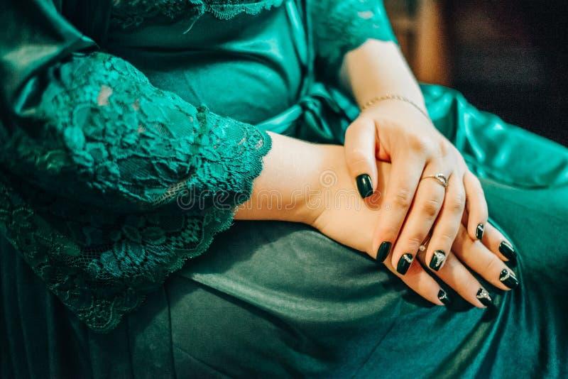 Διασχισμένα όπλα της νύφης σε μια εσθήτα επιδέσμου με ένα όμορφο μανικιούρ στα γόνατά της στοκ εικόνες