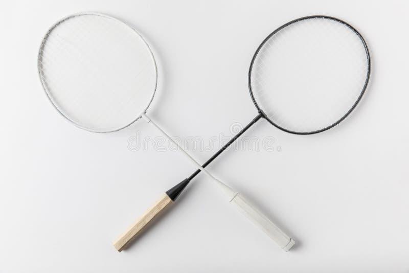 Διασχισμένες ρακέτες μπάντμιντον στην άσπρη επιφάνεια στοκ εικόνες