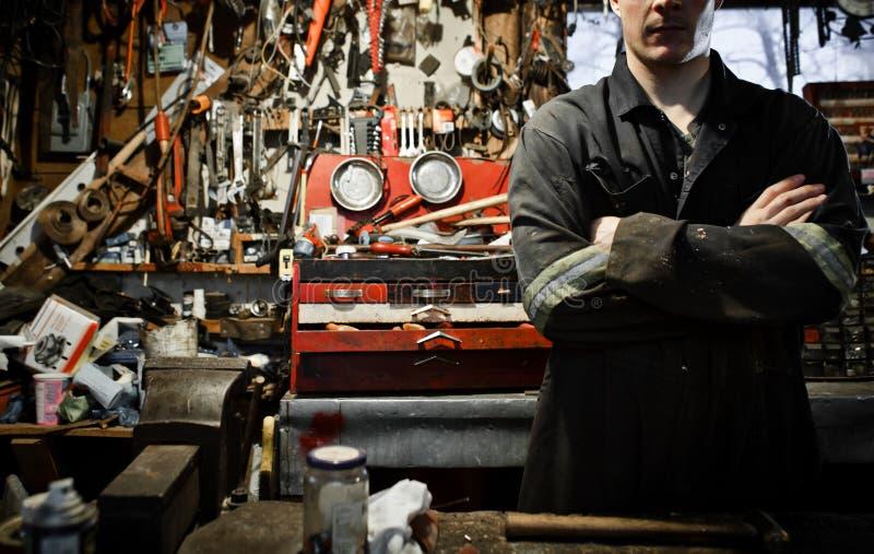 Διασχισμένος βραχίονας εργαζόμενος σε ένα υπόστεγο και τα μέρη της ένωσης εργαλείων στοκ φωτογραφίες