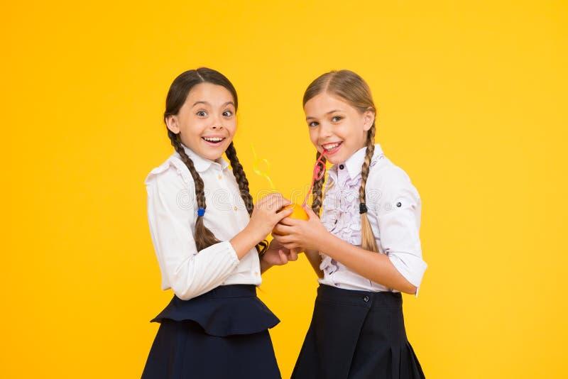 Διατροφή βιταμινών Σχολείο νωπών καρπών Σχολική στολή παιδιών κοριτσιών που πίνει τον πορτοκαλή φρέσκο χυμό φρούτων Διανομή μαθητ στοκ φωτογραφίες