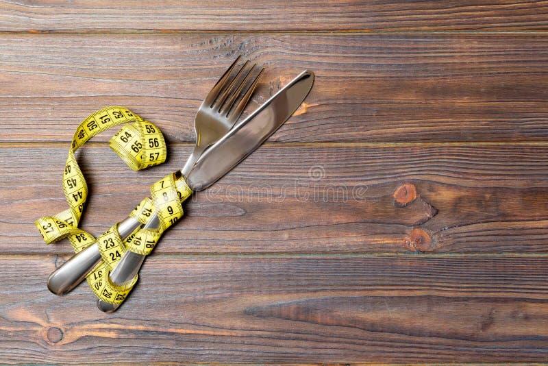 Διατροφή και υγιεινή έννοια κατανάλωσης με το διασχισμένα δίκρανο και το μαχαίρι και μέτρηση της ταινίας στο ξύλινο υπόβαθρο Τοπ  στοκ εικόνα