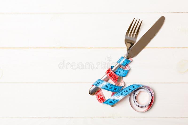 Διατροφή και υγιεινή έννοια κατανάλωσης με το διασχισμένα δίκρανο και το μαχαίρι και μέτρηση της ταινίας στο ξύλινο υπόβαθρο Τοπ  στοκ εικόνες