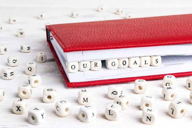 Διατυπώστε τους στόχους μας που γράφονται στους ξύλινους φραγμούς στο κόκκινο σημειωματάριο στο whi στοκ εικόνες με δικαίωμα ελεύθερης χρήσης