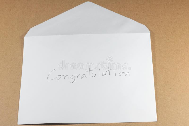 Διατύπωση των συγχαρητηρίων του άσπρου φακέλου στο καφετί υπόβαθρο στοκ εικόνες με δικαίωμα ελεύθερης χρήσης