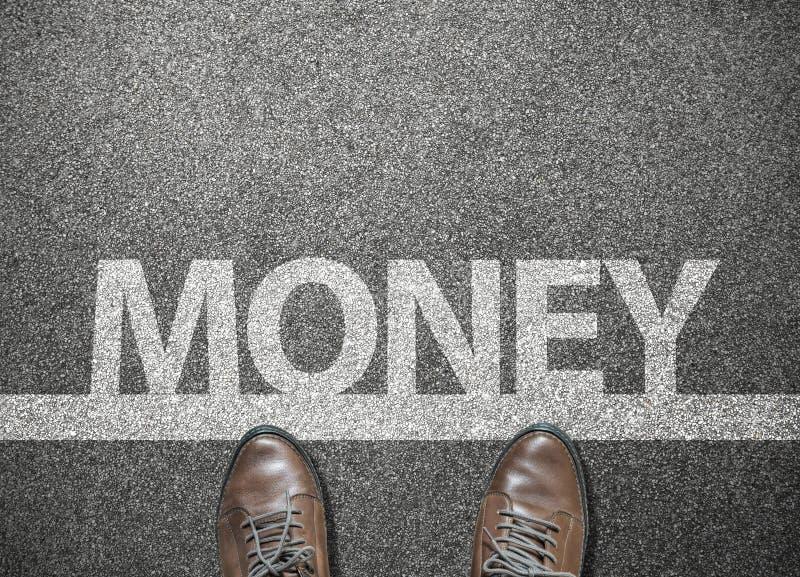 διατύπωση των χρημάτων στην οδική οδό με τα παπούτσια επιχειρηματιών στη γραμμή έναρξης στοκ φωτογραφίες