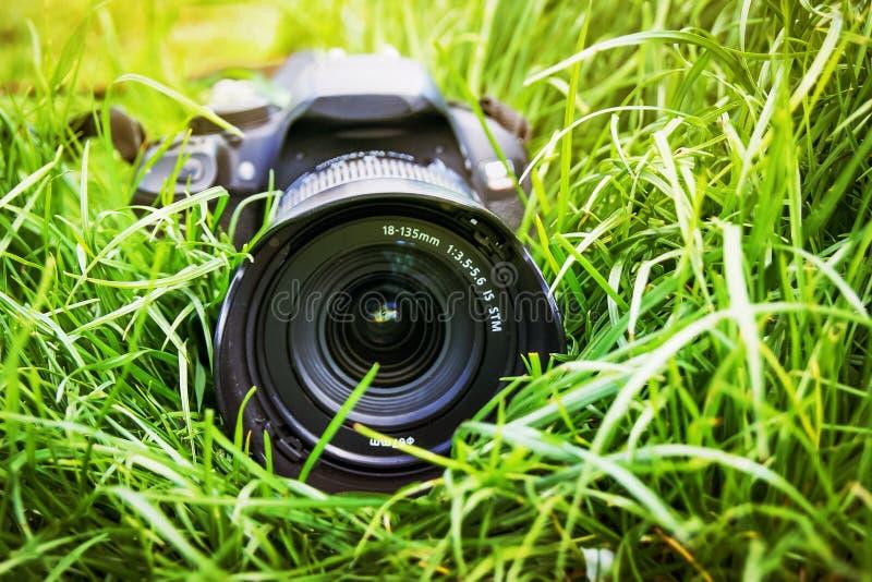 Διαφήμιση του επαγγελματικού φωτογραφικού εξοπλισμού Η κάμερα βρίσκεται στη χλόη στοκ εικόνα με δικαίωμα ελεύθερης χρήσης