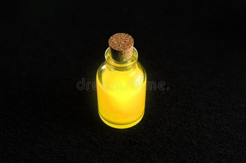 Διαφανές μπουκάλι με ένα δονούμενο χρυσό υγρό στοκ φωτογραφία