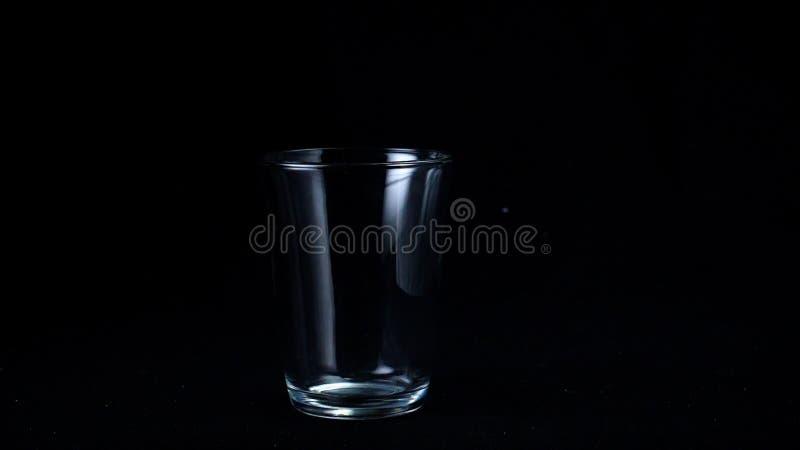 Διαφανές φλυτζάνι γυαλιού στο μαύρο υπόβαθρο Πλαίσιο Το γυαλί για το τσάι στέκεται κενό glint από το εξασθενημένο άσπρο φως επάνω στοκ φωτογραφίες