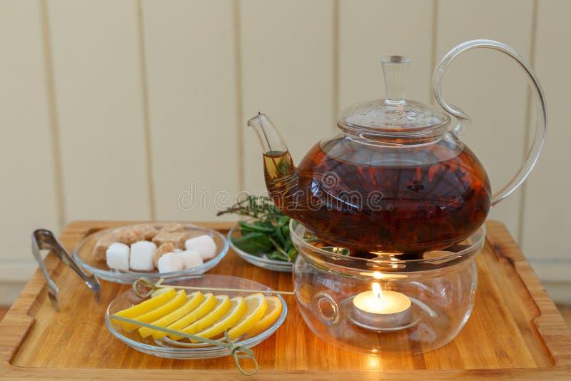 Διαφανής teapot κατσαρόλα με το νόστιμο μαύρο τσάι στη στάση με τα κεριά Στα πιάτα το λεμόνι, η ζάχαρη, η μέντα και το θυμάρι στο στοκ φωτογραφία με δικαίωμα ελεύθερης χρήσης
