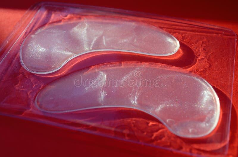 Διαφανή άσπρα καλλυντικά μπαλώματα ματιών στο διαφανές κιβώτιο στο κόκκινο υπόβαθρο, χωρίς πρόσωπο, στο φως του ήλιου στοκ εικόνα