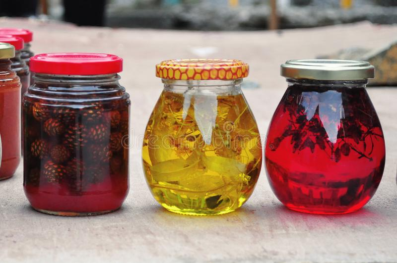 Διαφανή πολύχρωμα βάζα της κόκκινης και κίτρινης μαρμελάδας στοκ εικόνες