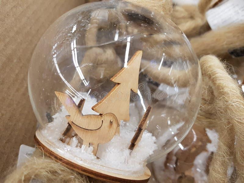 Διαφανείς σφαίρες γυαλιού με το τεχνητό χιόνι και ξύλινοι αριθμοί ενός πουλιού και fir-tree στοκ εικόνα