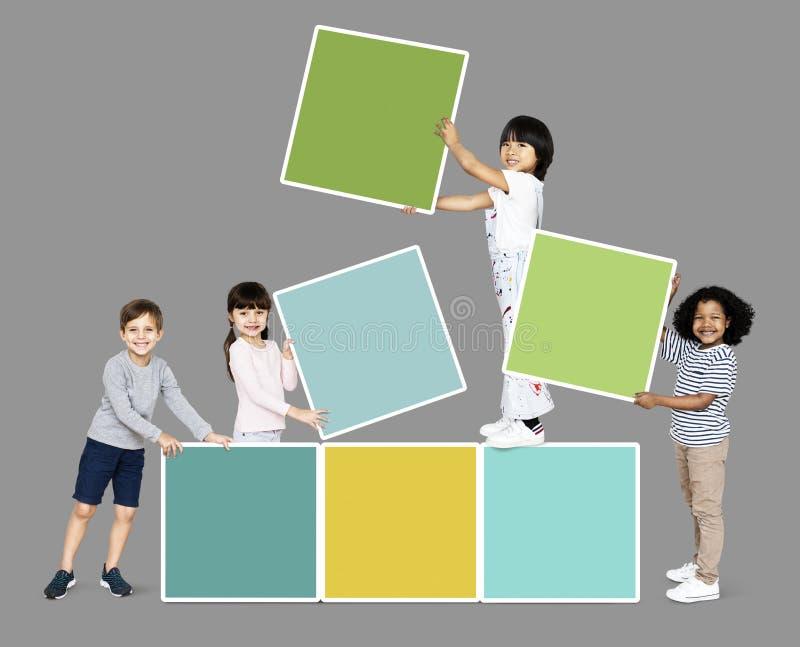 Διαφορετικά ευτυχή παιδιά που συσσωρεύουν τους κενούς τετραγωνικούς πίνακες στοκ εικόνα με δικαίωμα ελεύθερης χρήσης