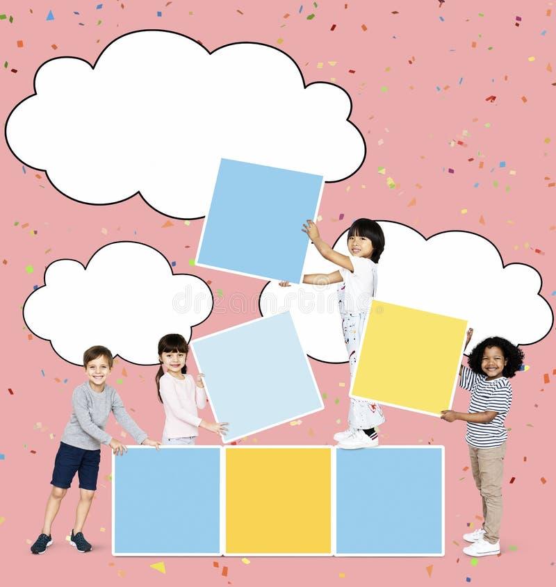 Διαφορετικά ευτυχή παιδιά που συσσωρεύουν τους κενούς τετραγωνικούς πίνακες στοκ φωτογραφίες