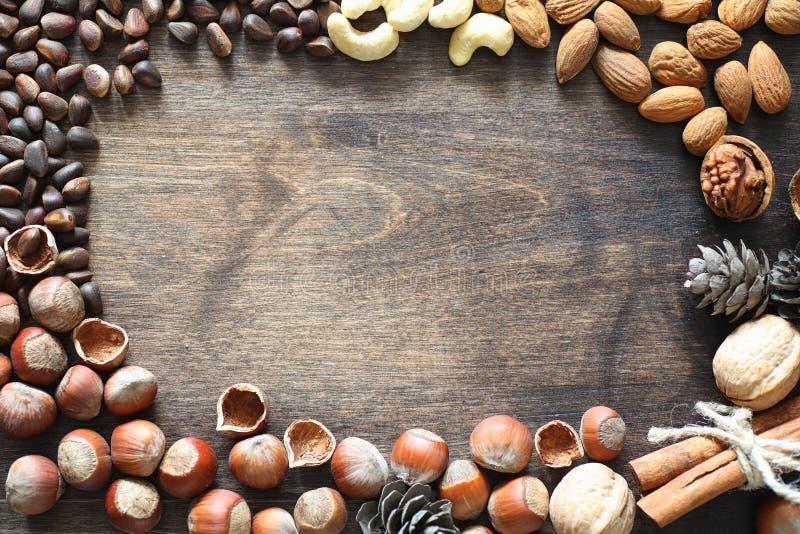 Διαφορετικά καρύδια σε έναν ξύλινο πίνακα Κέδρος, το δυτικό ανακάρδιο, φουντούκι, walnu στοκ φωτογραφία