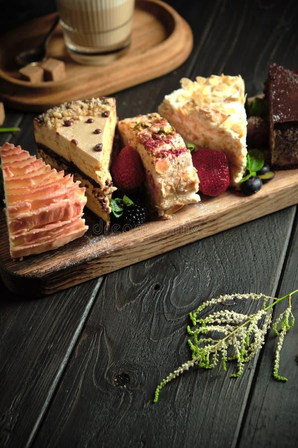 Διαφορετικά κομμάτια κέικ σε ένα ξύλινο πλακίδιο μενού τροφοδοσίας στοκ εικόνες