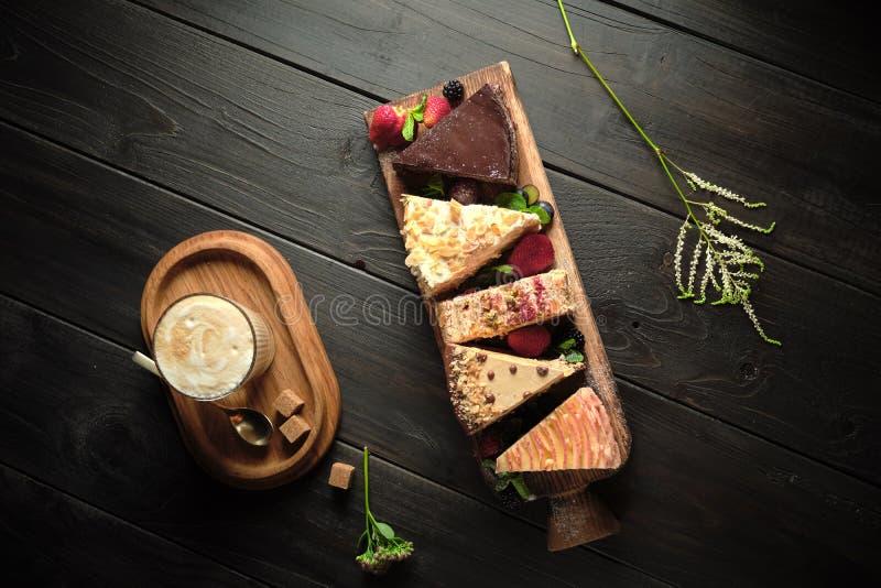 Διαφορετικά κομμάτια κέικ σε ένα ξύλινο πλακίδιο μενού τροφοδοσίας στοκ φωτογραφία