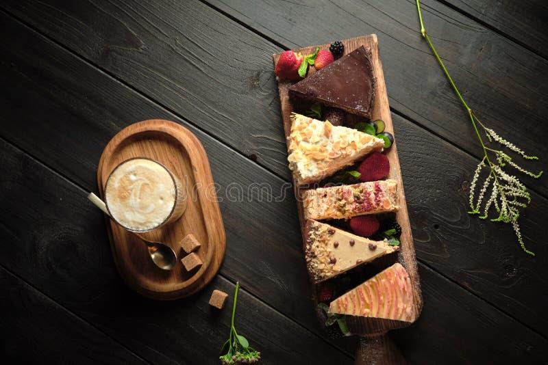 Διαφορετικά κομμάτια κέικ σε ένα ξύλινο πλακίδιο μενού τροφοδοσίας στοκ εικόνα