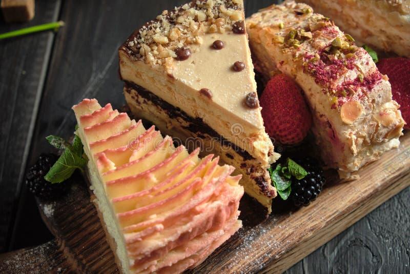 Διαφορετικά κομμάτια κέικ σε ένα ξύλινο πλακίδιο μενού τροφοδοσίας στοκ φωτογραφία με δικαίωμα ελεύθερης χρήσης