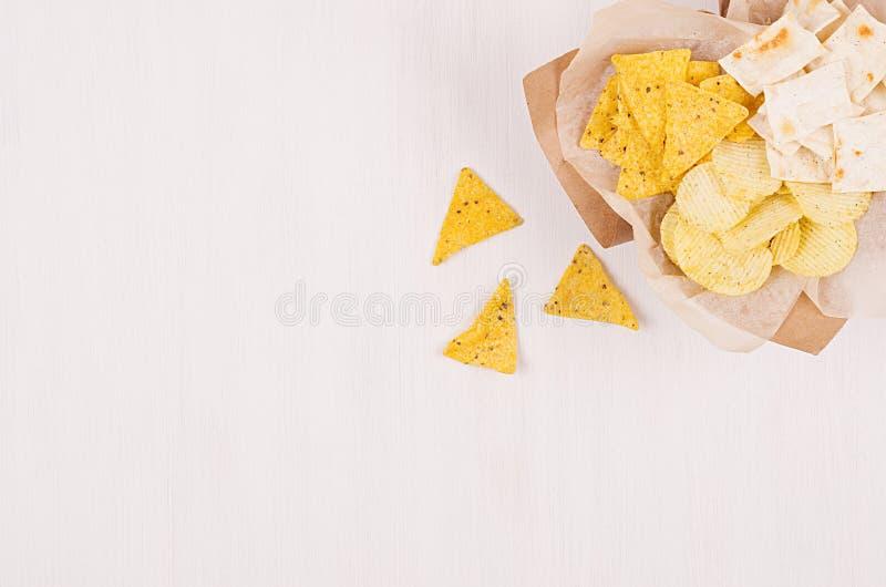 Διαφορετικά τριζάτα χρυσά πρόχειρα φαγητά σωρών σε χαρτί τεχνών, nachos τριγώνων στο μαλακό άσπρο ξύλινο υπόβαθρο, με το διάστημα στοκ εικόνες