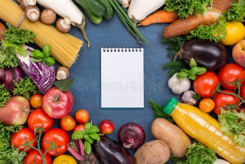 Διαφορετικά τρόφιμα με το σημειωματάριο με τις κενές σελίδες στοκ φωτογραφία με δικαίωμα ελεύθερης χρήσης