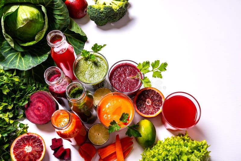 Διαφορετικά υγιή vegan ποτά με τα φρούτα και λαχανικά στο άσπρο ξύλινο υπόβαθρο r στοκ εικόνες