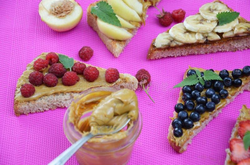 διαφορετικές εύγευστες φρυγανιές στο πράσινο ή ρόδινο πορφυρό υπόβαθρο Υγιές σάντουιτς για το πρόγευμα ή το πρόχειρο φαγητό Φρυγα στοκ εικόνα με δικαίωμα ελεύθερης χρήσης