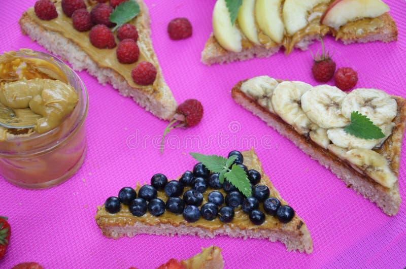 διαφορετικές εύγευστες φρυγανιές στο πράσινο ή ρόδινο πορφυρό υπόβαθρο Υγιές σάντουιτς για το πρόγευμα ή το πρόχειρο φαγητό Φρυγα στοκ εικόνες με δικαίωμα ελεύθερης χρήσης