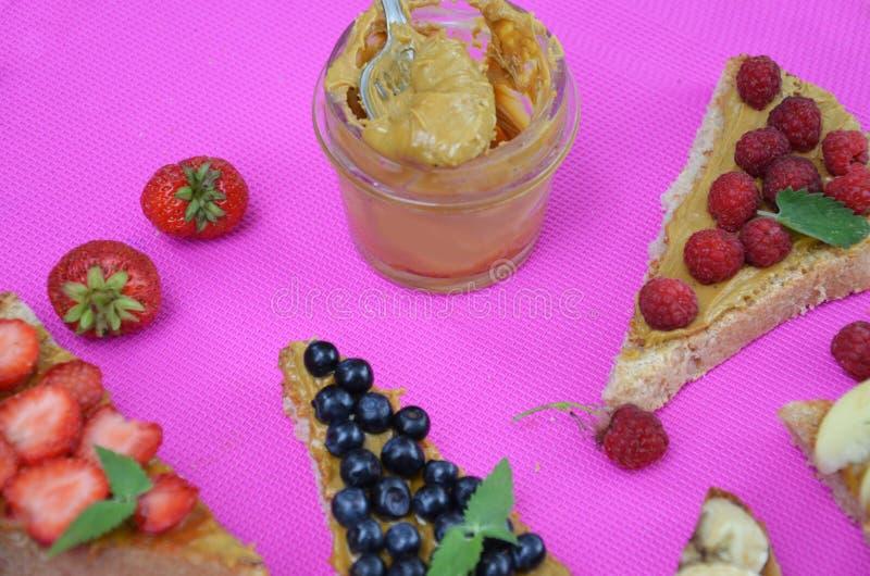 διαφορετικές εύγευστες φρυγανιές στο πράσινο ή ρόδινο πορφυρό υπόβαθρο Υγιές σάντουιτς για το πρόγευμα ή το πρόχειρο φαγητό Φρυγα στοκ εικόνα