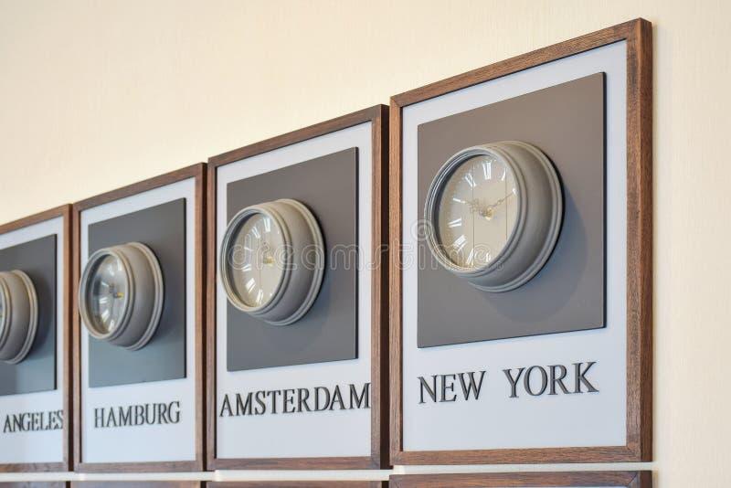 Διαφορετικές διαφορές ώρας ρολογιών στον τοίχο στοκ εικόνες