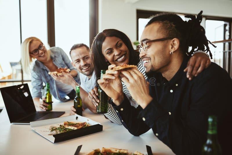 Διαφορετική ομάδα γελώντας συναδέλφων γραφείων που έχουν την πίτσα και τη μέλισσα στοκ εικόνες