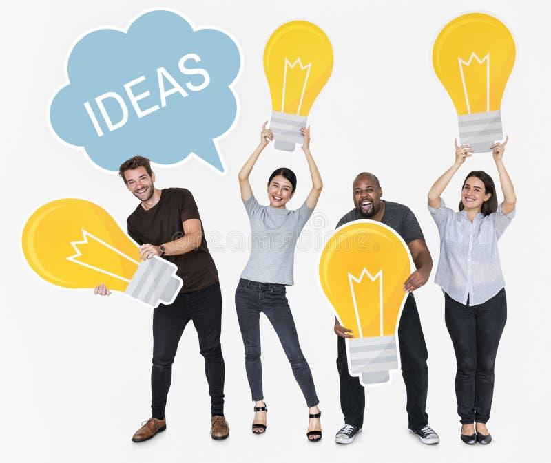 Διαφορετικοί άνθρωποι με τις νέες ιδέες και τις λαμπρές λάμπες φωτός στοκ φωτογραφία