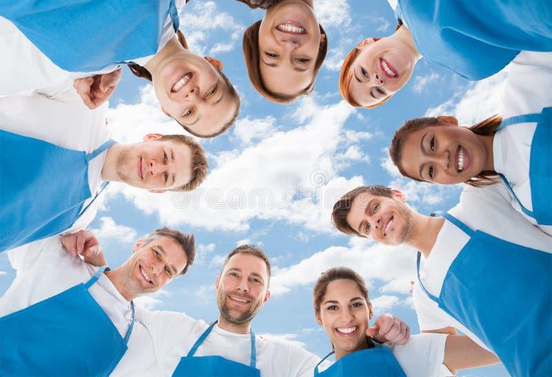 Διαφορετικοί επαγγελματικοί καθαριστές που στέκονται στη συσσώρευση ενάντια στον ουρανό στοκ εικόνες
