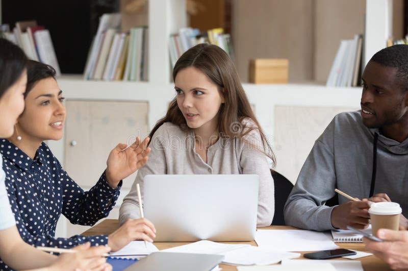 Διαφορετικοί νέοι στο κοινό γραφείο που μελετούν από κοινού στοκ εικόνα