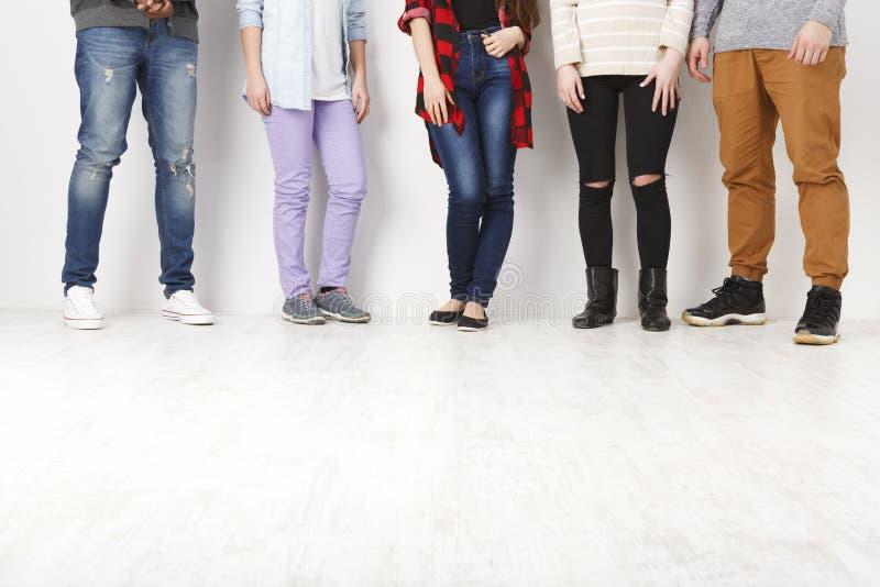 Διαφορετικοί περιστασιακοί άνθρωποι που στέκονται στη σειρά εσωτερική, συγκομιδή στοκ εικόνες