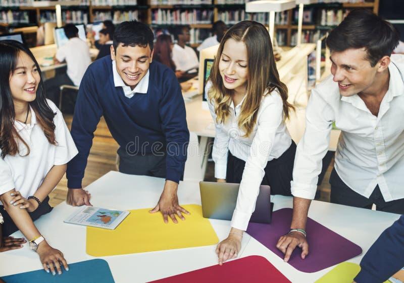 Διαφορετικοί σπουδαστές που μαθαίνουν τη μόνιμη έννοια βιβλιοθήκης στοκ εικόνες