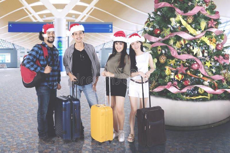 Διαφορετικοί τουρίστες με το χριστουγεννιάτικο δέντρο στο τερματικό αερολιμένων στοκ εικόνες