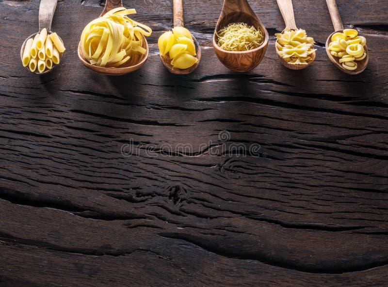 Διαφορετικοί τύποι ζυμαρικών στα ξύλινα κουτάλια στον πίνακα Τοπ όψη στοκ εικόνες