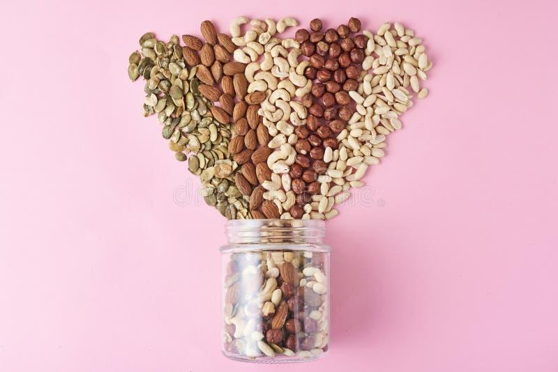 Διαφορετικοί τύποι καρυδιών και σπόρων σε ένα βάζο γυαλιού στο ρόδινο υπόβαθρο, τοπ άποψη στοκ φωτογραφία με δικαίωμα ελεύθερης χρήσης