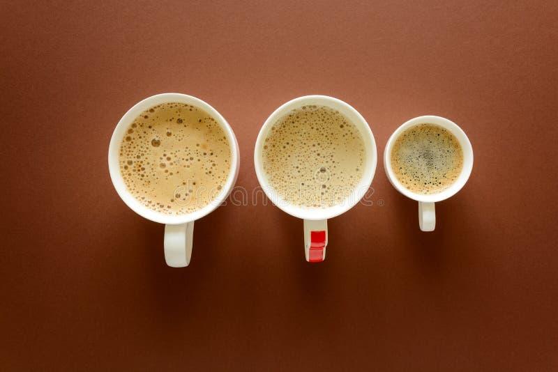 Διαφορετικοί τύποι καφέδων Αργά, cappuccino και espresso στο καφετί υπόβαθρο Τοπ όψη Επίπεδος βάλτε στοκ φωτογραφία