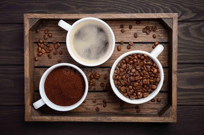 Διαφορετικοί τύποι καφέ - που αλέθονται, σιταριών και ποτών στο σκοτεινό ξύλινο υπόβαθρο στοκ φωτογραφίες με δικαίωμα ελεύθερης χρήσης
