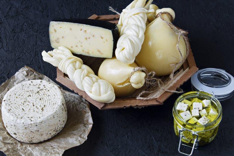 Διαφορετικοί τύποι τυριών σε ένα μαύρο υπόβαθρο Πιατέλα τυριών στοκ φωτογραφίες