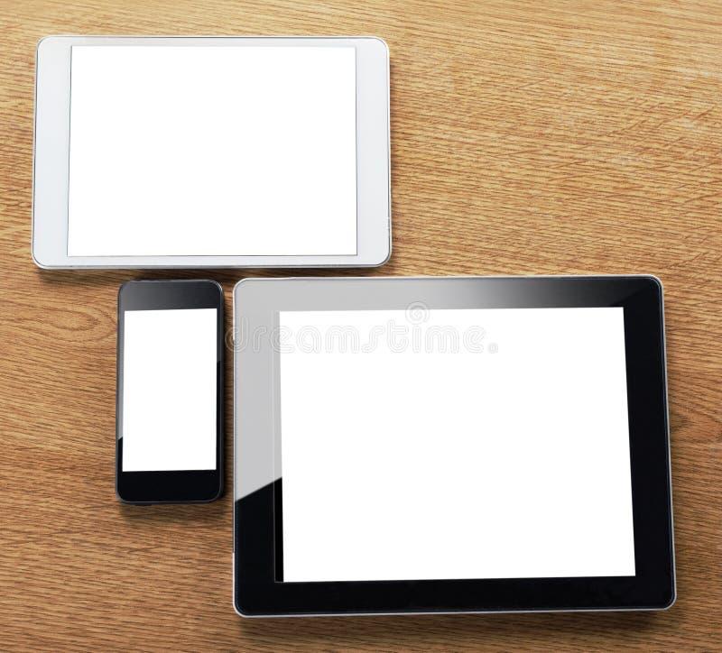 Διαφορετικοί τύποι ψηφιακών ταμπλετών και έξυπνων τηλεφώνων σε έναν υπολογιστή γραφείου στοκ εικόνα