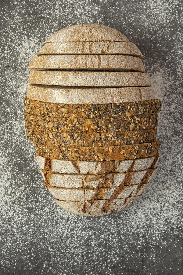 Διαφορετικοί τύποι ψωμιών που τεμαχίζονται σε ένα σκοτεινό υπόβαθρο που ψεκάζεται με το αλεύρι στοκ εικόνα